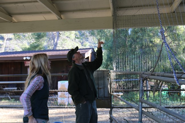 Jeff Sikich pointing at animal enclosure