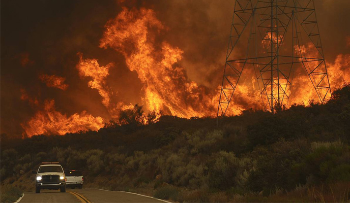 Wildfire approaching transmission lines with two trucks in foreground