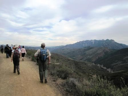 Hikers travel along the Backbone Trail and look towards the rugged cliffs of the Circle X Ranch area.