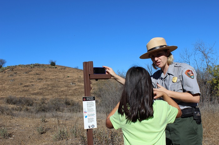 Ranger interacts with a youth and demonstrates how to use a photo-monitoring station