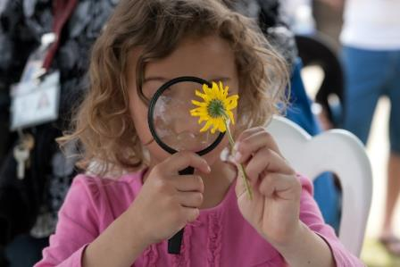 Girl inspects flower with magnifying glass.