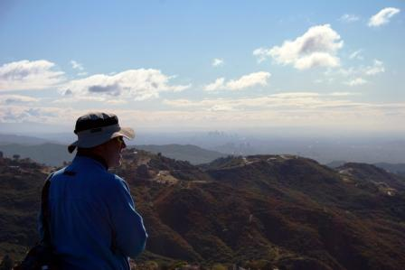 A hiker enjoys the view from a lookout just below Saddle Peak. Out in the distance is Downtown Los Angeles.