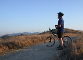 A mountain biker, dressed in helmet and bike gear is standing with his bike on a fire road trail, as the Simi Hills of Cheeseboro Canyon roll out in front of him.