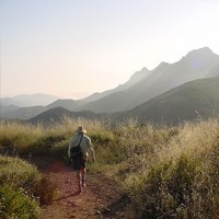 A late-afternoon hiker walks along a trail as mountains fade into the horizon