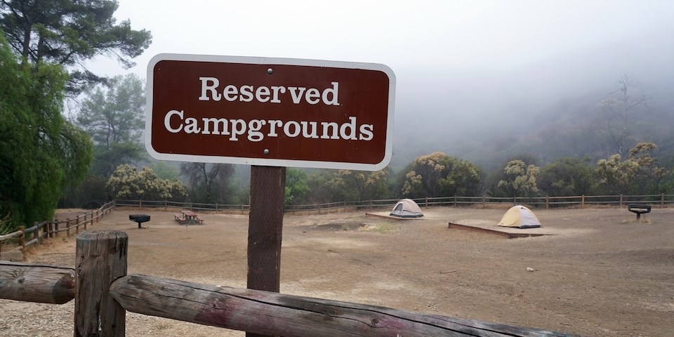 Reserved Campgrounds sign in front of the foggy campsite with two tents