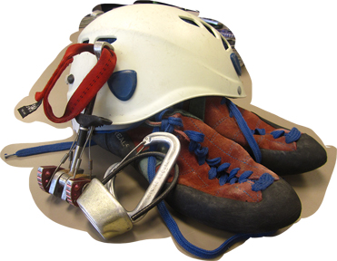 A climbers helmet, hardware, and shoes are ready for a day of climbing.