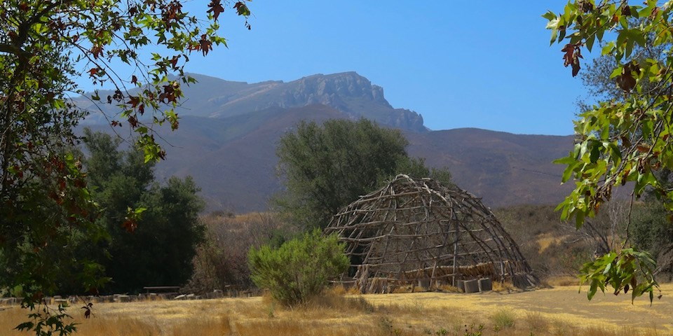 Framed by trees is an 'ap, a wooden Chumash structure in front of Boney Mountain in the distance