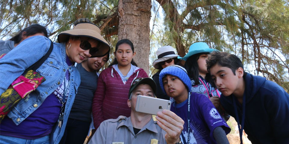 A group of young people gather around a ranger to look at a smartphone