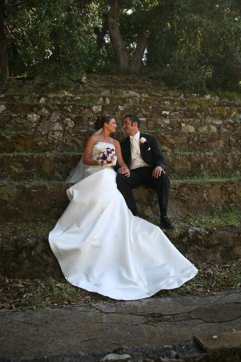 A couple enjoys a romantic moment in the park on their wedding sitting on the steps at Peter Strauss Ranch.