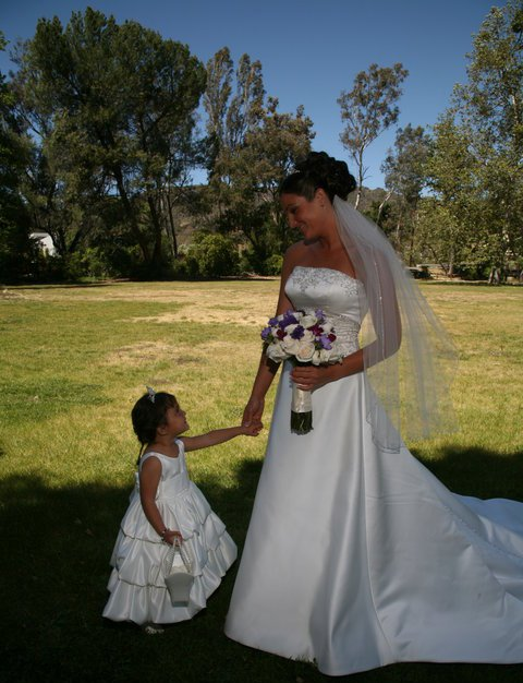A bride and her flower girl share a special memory together at Peter Strauss Ranch.