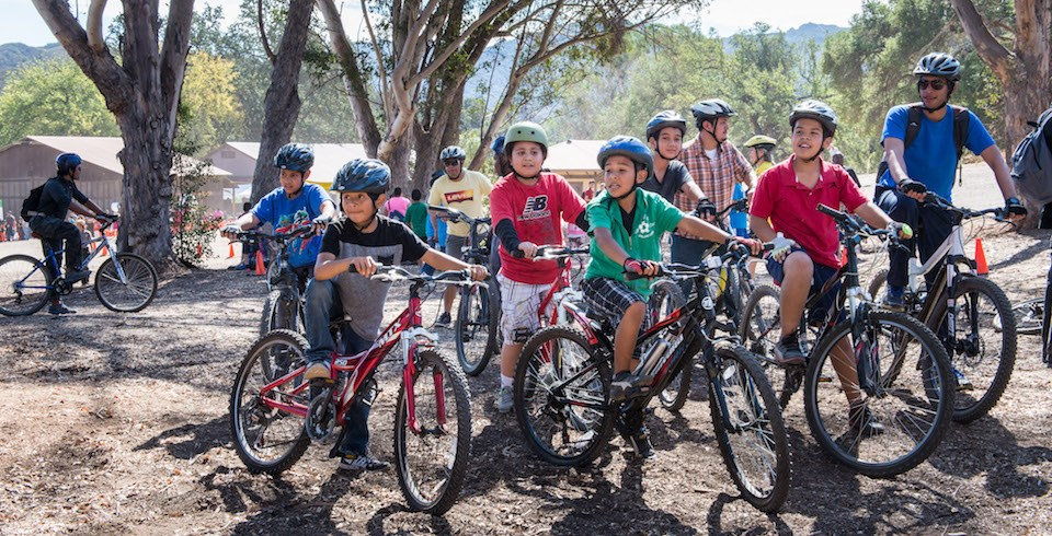 A group of youth stand with their mountain bikes
