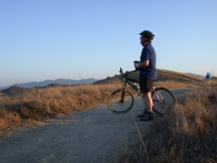 A mountain biker takes a moment to enjoy views of the park from a rise.