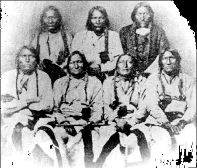 Picture of seven Cheyenne and Arapaho Chiefs at the Camp Weld Conference. Black Kettle is seated holding a pipe.
