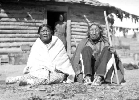 Ellen and Arthur Brady, both survivors of the Sand Creek Massacre at their home on the Northern Cheyenne reservation in Montana. Their daughter Mary stands in the doorway.