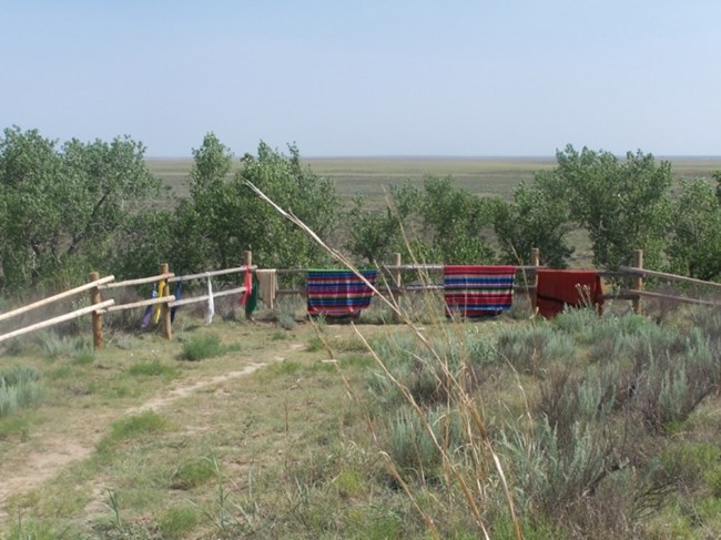 Tribal blankets over the fence on Monument Hill at Sand Creek Massacre NHS.