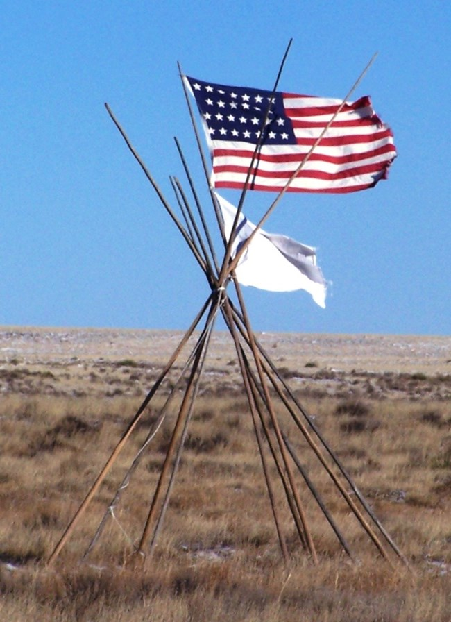 33-Star American Flag, white flag, atop a tipi frame at Sand Creek Massacre National Historic Site.