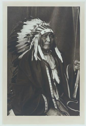 Brave Bear, Cheyenne Indian.  Died near Thomas, Oklahoma in 1932. He is seen here in tribal clothing and head dress. He clutches a bow in his left hand.