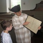 A boy examines a map of family pews.