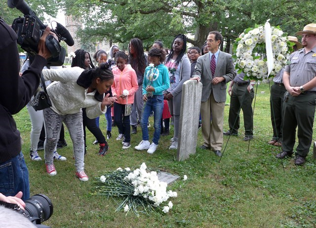 At a celebration of the renaming of two local schools after Rebecca and Benjamin Turner, local students lay flowers at the grave site of Rebecca Turner in the cemetery of St. Paul's Church.