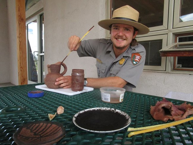 Ranger Davis slipping a pot with a Yucca brush.