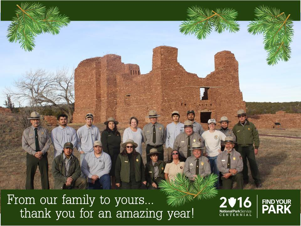 Approximately 20 people, some in NPS ranger uniforms, stand in front of the remains of a stone mission. Caption on image: From our family to yours...thank you for an amazing year!