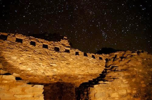 A starry night sky surrounds the ruins of a stone mission.