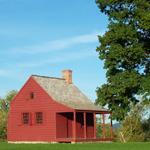A small, red, one-room farmhouse.