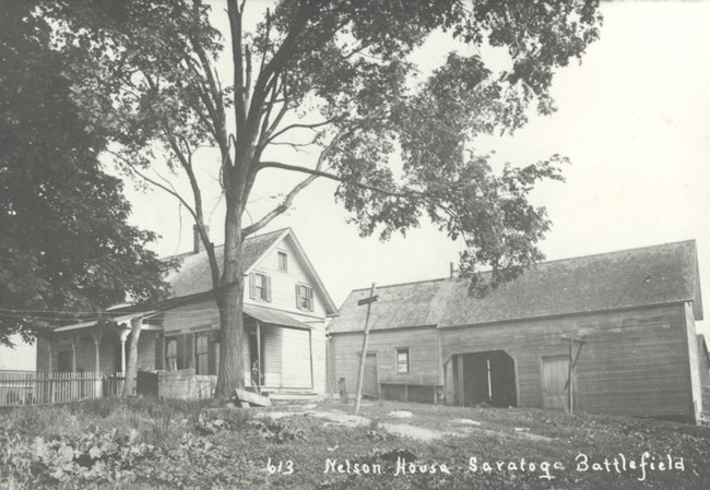 Black and white image of house and outbuildings circa 1920