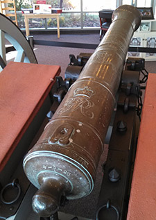 Close-up view of a Revolutionary War cannon on its wooden carriage. Two reddish wooden boxes flank the cannon, one to either side.