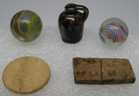 Close-up photo of five 18th and 19th century toys: two marbles, a doll-sized brown stoneware jug, a rounded bone game piece, and a wooden domino.