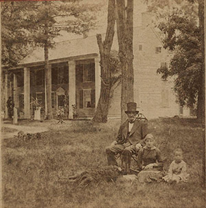 Halftone photo of historic, Revolutionary War era house with older gentleman in suit and stovepipe hat posed seated with two younger children and the family dog on the front lawn of this two-story, four column-faced house.
