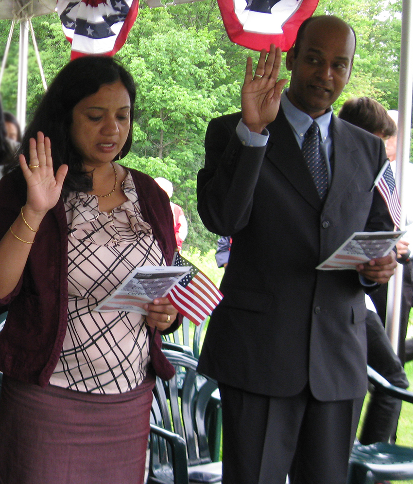 Two new U.S. citizens, a woman and a man, being sworn in.