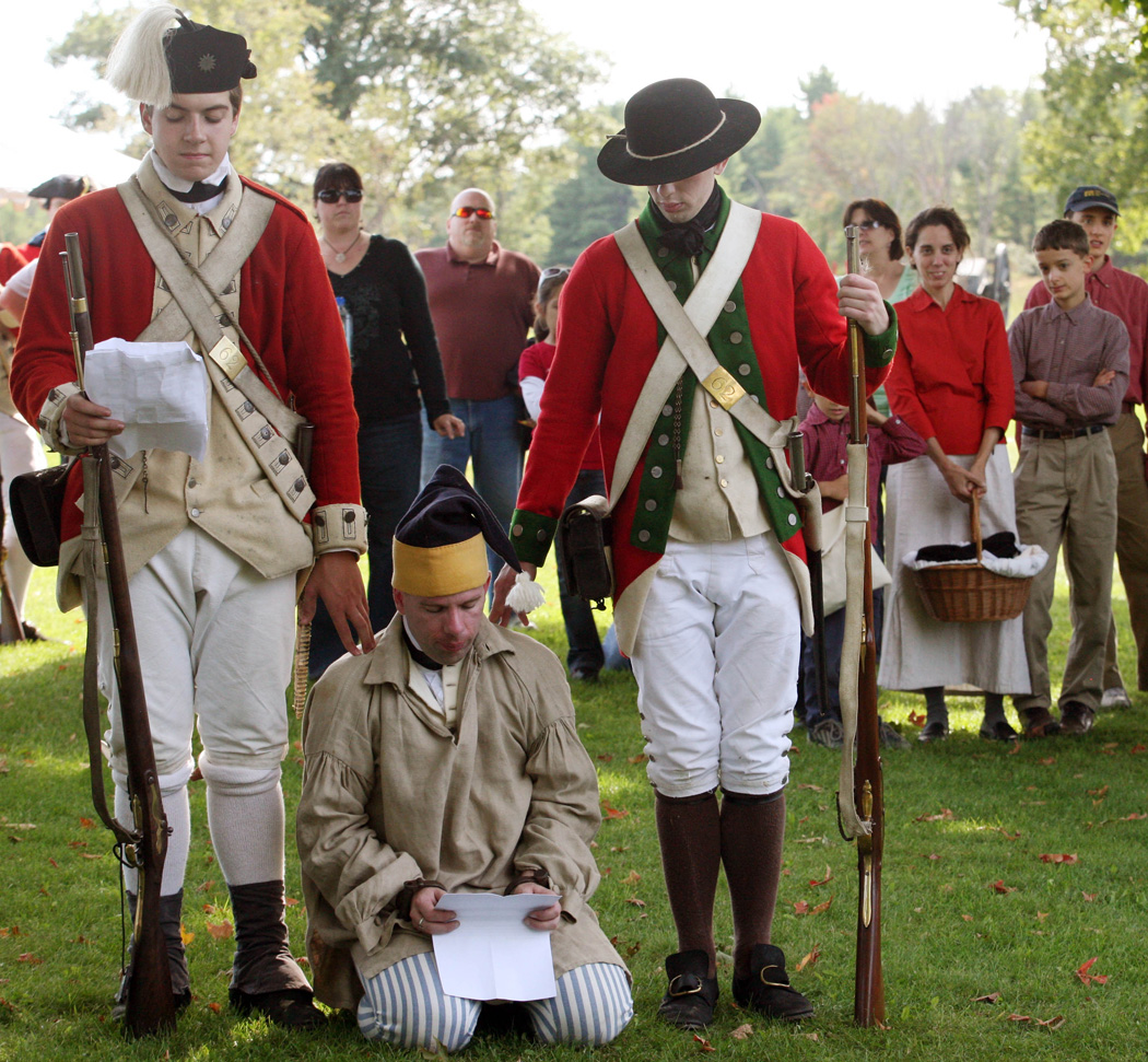Revolution spy kneeling on the ground surrounded by two standing soldiers