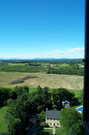 View from the top of Saratoga Monument, with clear, deep blue skies, rich green trees and lawn, light brown farm fields, and faded green hills in the distance.