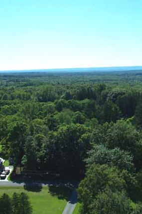 View looking west.  The dark green trees seem to dominate the landscape, though actually much development has occurred throughout the area, from farming to urbanization in the city of Saratoga Springs, New York.  The pale blue skies hang gently over the landscape, a contrast to the deep green of the trees.