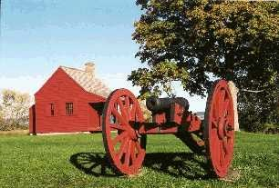 John Neilson Farmhouse, only standing building on the battlefield from the time of the Battles of Saratoga.  Small red farmhouse in background, with a cannon on a red carriage in the foreground.