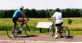 Two bicyclists stop to read a sign describing the scene in front of them.