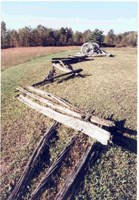 A mown field features a collapsed wooden