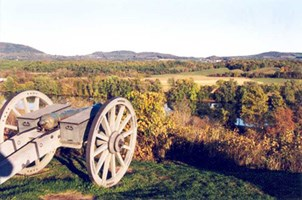 A lone cannon sits on a hill overlooking the Hudson River.  An explosion of autumn foliage adorns the river valley.