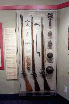 Section of Revolutionary War Timeline Exhibit.  Pictured here are several muskets, soldiers' implements, and artillery rounds and tools.