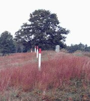 Image of several white marker posts with red tops depicting where the wooden defensive wall of the Breymann Redoubt once stood.