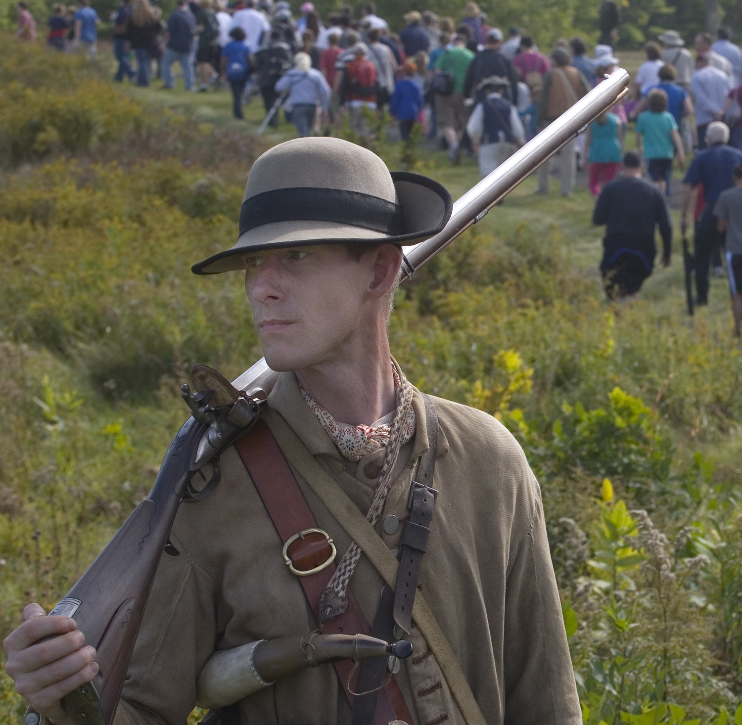 Colonial soldier holding musket, crowd of visitors in background