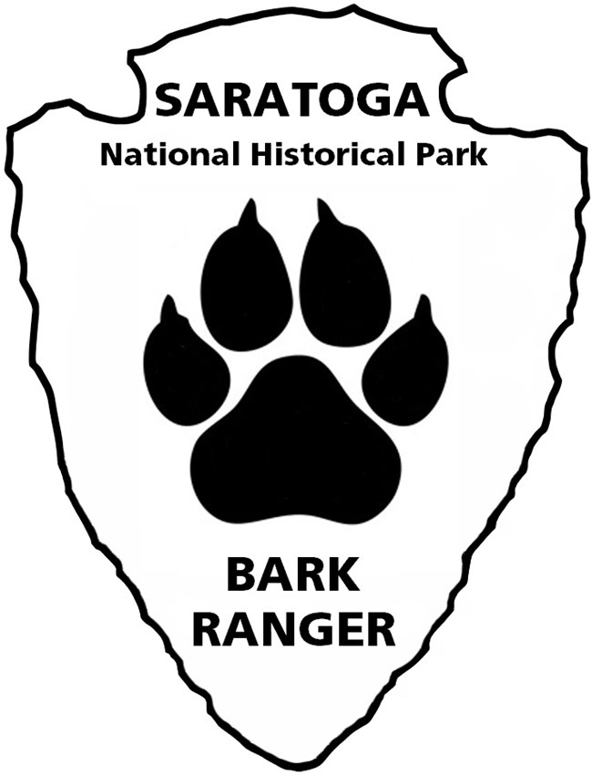 Arrowhead outline with paw print in middle and text reading Saratoga National Historical Park Bark Ranger
