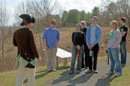 A Battlefield Guide in Revolutionary War American uniform speaks with a group of visitors.