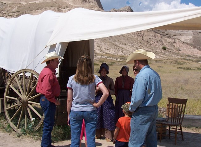 Living history volunteers and visitors at covered wagon
