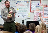 A ranger speaks with children in a classroom