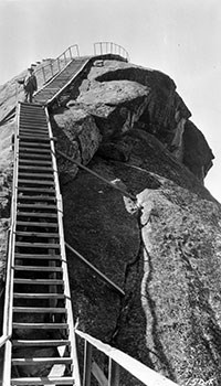 Steep and narrow wooden stairs lead up a rock face to the top of a granite dome.