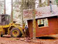 front-end loader lifts a cabin off its foundation