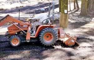 Small front end loader decompacts soil.