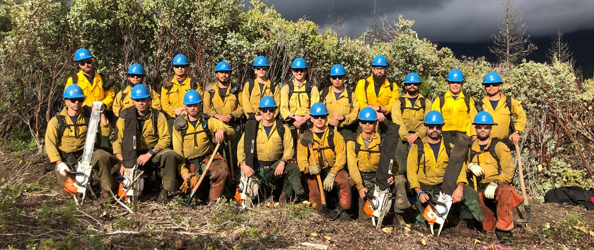 19 Arrowhead Hotshots pose in two rows for a crew photo